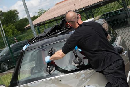 windscreen: Glazier handling car windshield or windscreen made of glass in garage Stock Photo