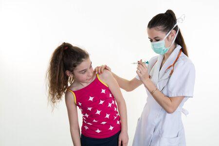 inyeccion intramuscular: pediatra doctora con m�scara de respiraci�n sobre la boca dando ni�o una inyecci�n intramuscular en el brazo