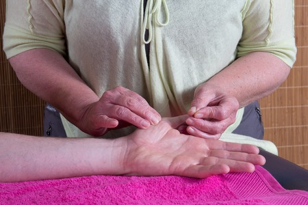 tcm: Two silver acupuncture needles inserted into the top of a hand resting on a white towel