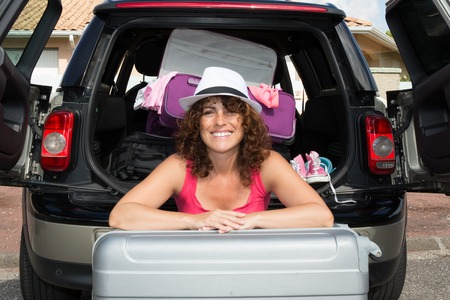 go for: Woman ready to go for holidays in a trunk of a car