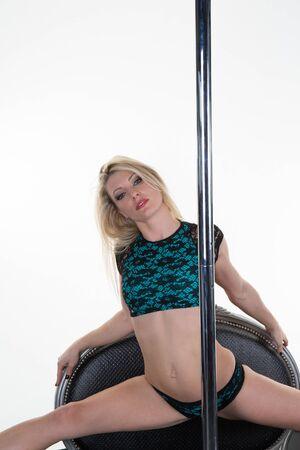 pole dance: Giovane donna sottile pole dance isolato