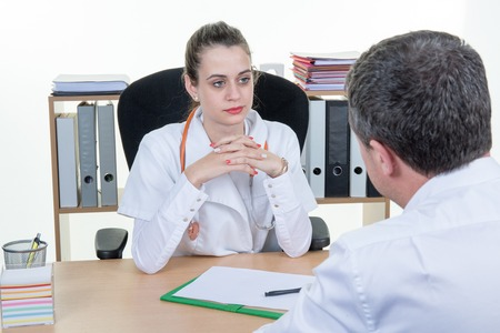 medico y paciente: Doctor positivo que recibe paciente enfermo en la oficina y el cuestionamiento Foto de archivo
