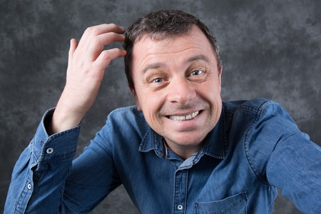 foolish: Funny and foolish man isolated on a grey background