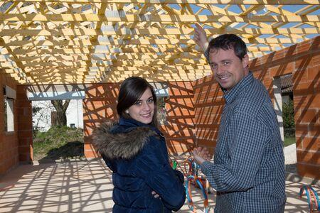 Coppia felice di stare insieme dentro la loro casa in costruzione.