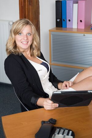 feet on desk: Casual businesswoman having a tablet with her feet up at desk in her office Stock Photo