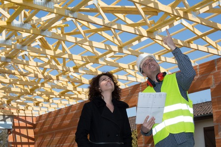 Female and male building engineer discussing building plans standing over unfinished brick house with wooden roof structure