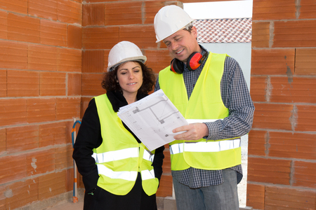 partnership security: Construction manager and engineer working on building site