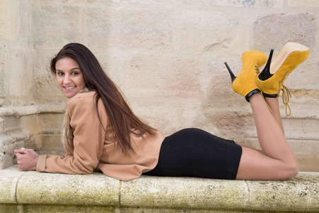 woman laying down: Attractive elegant young woman laying down on stone bench, looking at camera Stock Photo