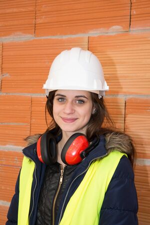 portrait of female bricklayer under a site of construction