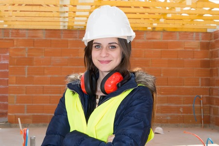 tradeswoman: Smiling woman working on a construction site crossed arms