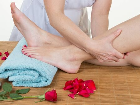 traditional healer: Beautiful young woman getting feet massage treatment at spa center Stock Photo