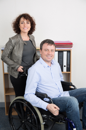 workteam: Business man in wheelchair with assistant in office