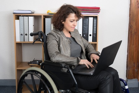 self assured: Confident disabled woman sitting and working with laptop