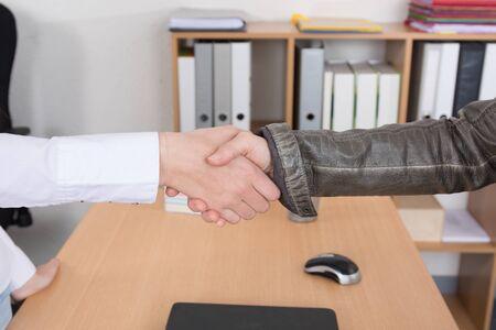 indoors: Two Businesspeople shaking hands indoors Stock Photo