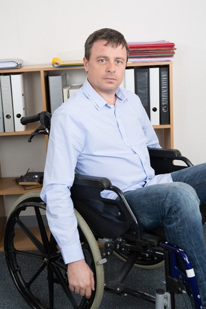 paraplegic: man in wheelchair in office is using his laptop, disabled young man is surfing in internet