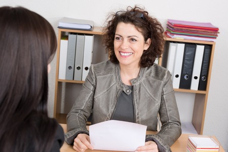 two persons only: Businesswoman conducting a job interview seated at her desk in her office holding a folder and smiling