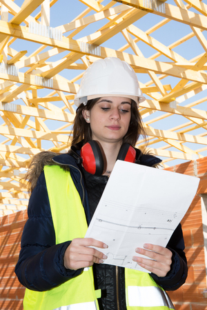 30 35 years: female engineer looking at blueprints in construction site