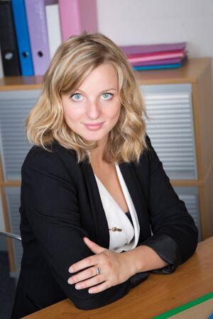 workteam: Attractive businesswoman sitting in office with workteam