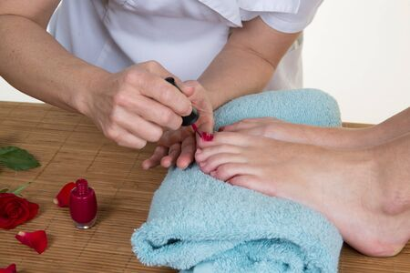 toenails: Close-up of pedicurist applying nail polish to the toenails