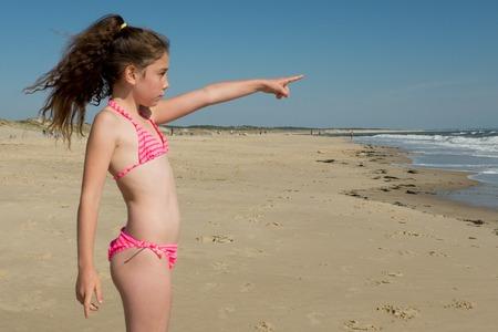 niña señalando al mar en la playa tropical de la isla Foto de archivo