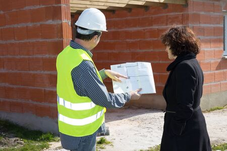 female architect: Construction: female architect review plans with builder.