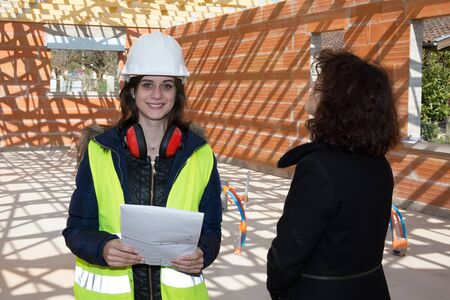 female architect: Female architect and client looking at under construction building