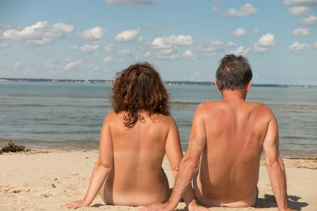 nude woman sitting: Nude family sitting on the beach. Stock Photo