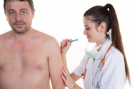h1n1 vaccination: Young doctor women give an injection to a man shirtless