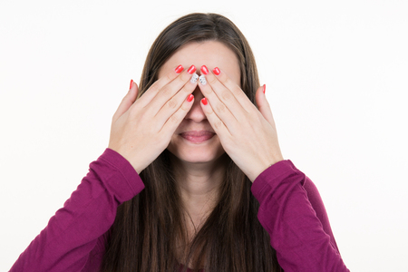 obscured face: Young brunette woman covering face using her both hands