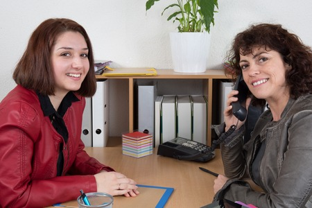 one on one meeting: Two businesswomen at the meeting, one with a phone