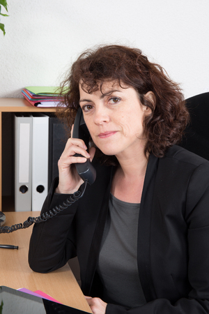 mid age: Mid age businesswoman on phone at desk