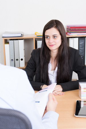 examined: Business interview of young woman examined by man professional manager Stock Photo