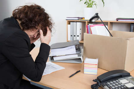 desperation: Fired employee holding her head in desperation with her box on the desk