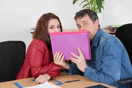 chismes: equipo de negocios ocasional cotilleando en el escritorio en la oficina
