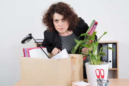 despairing: Portrait of a sad fired woman with box of personal items isolated on white background Stock Photo