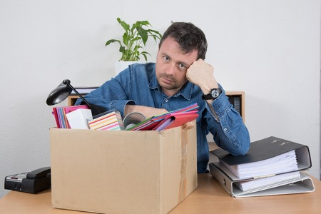 layoff: Businessman Packing Files In a Box At Office