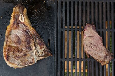 barbecuing: Big tasty beef steak cooking over flaming grill Stock Photo