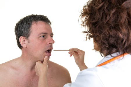 groping: Doctor auscultating the throat of a patient in an examination room