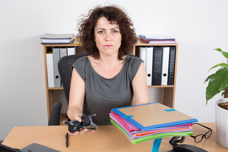 resignation: Woman hand holding headphones, folders and resignation letter on the desk Stock Photo