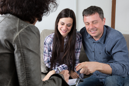 purchasers: Happy woman taking paper to new house. agent giving plan to young couple purchasing new house