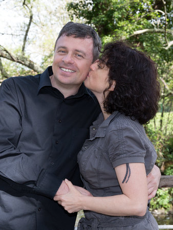 cuddle: Loving and cuddle  middle aged couple outdoors, woman kiss Stock Photo