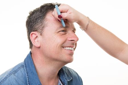 tweezers: Closeup of man with tweezers plucking eyebrows