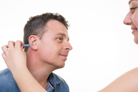plucking: Closeup of man with tweezers plucking ears