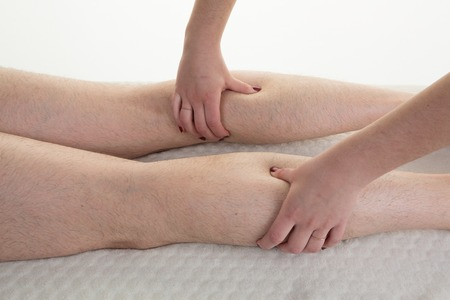 treating: Adult male physiotherapist treating the leg of male patient. Stock Photo