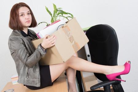 layoffs: Upset business woman carrying office belongings after loosing job