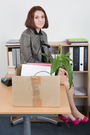tearful: Upset business woman carrying office belongings after loosing job
