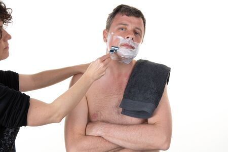 beauty center: At beauty center a woman is shaving a man isolated Stock Photo