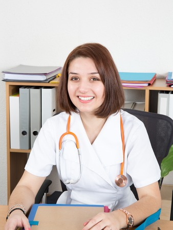 a lady doctor: Portrait of young female doctor sitting at desk in hospital