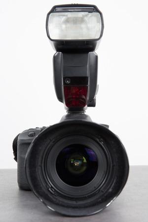 Photo camera flash with camera on grey Reklamní fotografie