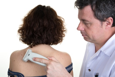 healthcare facilities: Handsome doctor using an ultrasound machine on woman back